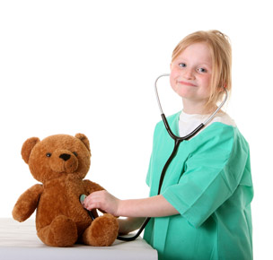 child playing with stethoscope and teddy bear